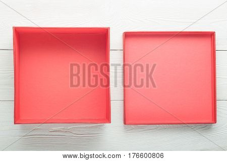 Opened empty red box with lid on white wooden background. Flat lay. Top view with copy space