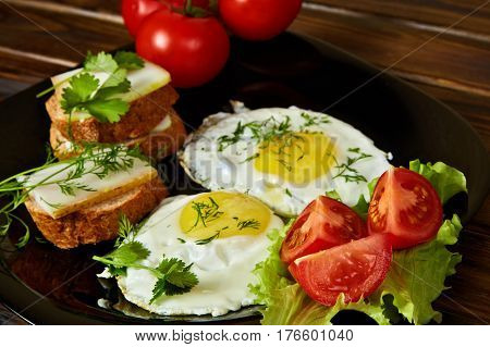 Scrambled eggs with greens and fresh tomatoes on a black plate