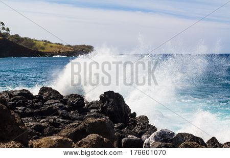 Waves crashing against the rocks on the northwest coast of the Big Island of Hawaii on a sunny day.
