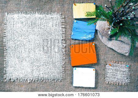 Rectangle pieces of white burlap and wood pinned as frames on gray burlap background. Spring bunch of twigs of apple tree and fur tree in the corner. Rustic style eco-friendly universal template
