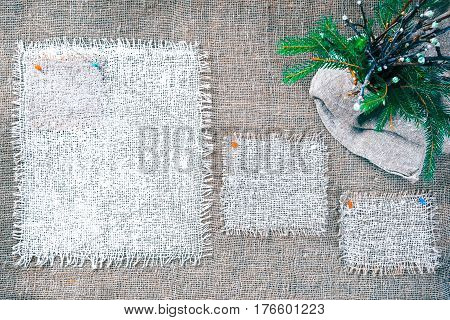 Rectangle pieces of white burlap pinned as various frames on gray burlap background. Spring bunch of twigs of apple tree and fur tree in the corner. Rustic style eco-friendly universal template