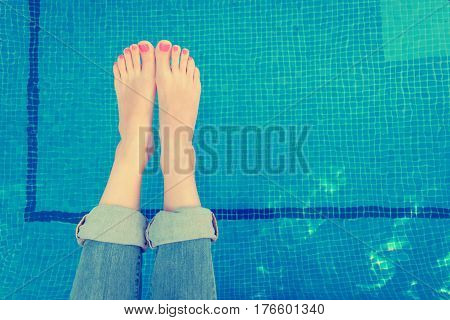 Above view on woman legs rolled up jeans while relaxing by the swimming pool