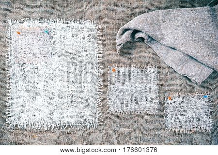 Rectangle pieces of white burlap pinned as various frames on gray burlap background. Draped canvas in the corner. Rustic style eco-friendly universal template