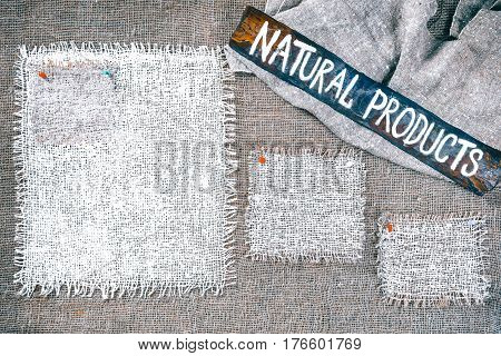 Rectangle pieces of white burlap pinned as various frames on gray burlap background. Wood signboard with text 'Natural products' on draped canvas in the corner. Rustic style eco-friendly template