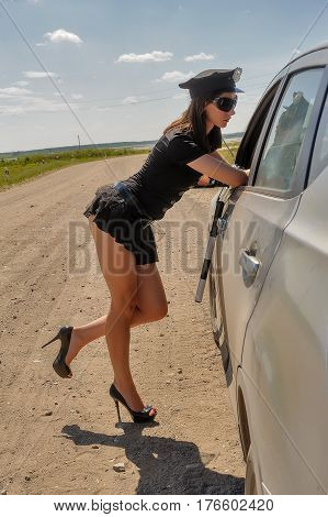 Young attractive police woman checking driver license
