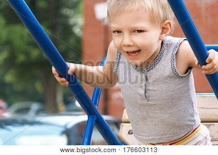 Blond boy with open mouth rides on seesaw