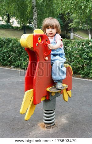 Baby riding on hutches at the playground with disheveled hair