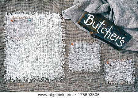 Rectangle pieces of white burlap pinned as various frames on gray burlap background. Wood signboard with text 'Butchers' on draped canvas in the corner. Rustic style eco-friendly template
