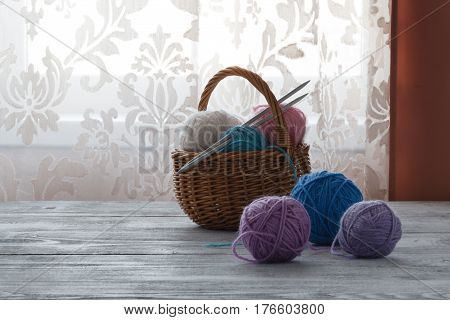 Multicolored clews in wicker basket closeup on table