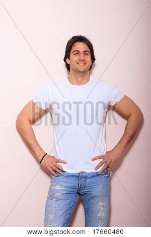portrait of a young man blue jeans and white tshirt  over light wall