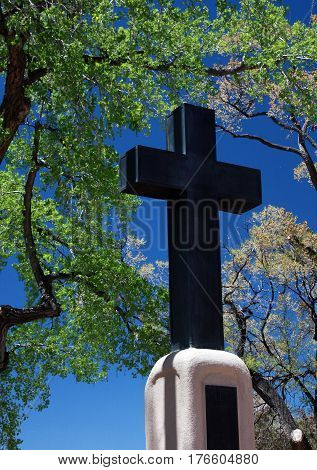 A large crucifix sculpture on top of veterans memorial in Taos, NM in the center of the plaza.