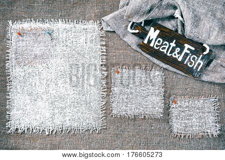 Rectangle pieces of white burlap pinned as various frames on gray burlap background. Wood signboard with text 'Meat and fish' on draped canvas in the corner. Rustic style eco-friendly template