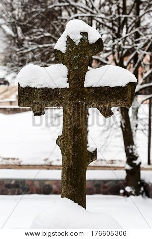 Christian cross covered with snow on the Rasos cemetery in Vilnius Lithuania