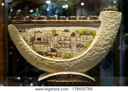 TIBERIAS ISRAEL - FEBRUARY 26 2017: Chanukah candlestick in the window of the souvenir shop. Design of Chanukiah contains a shofar and a stylized drawing of the houses of Jerusalem