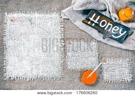 Rectangle pieces of white burlap pinned as frames on gray burlap background. Wood signboard with text 'Honey' and jar of honey on draped canvas in the corner. Rustic style eco-friendly template