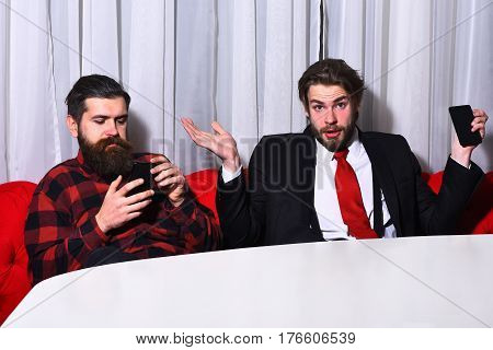 bearded men businessmen long beard brutal caucasian hipster with moustache hold mobile or cell phone has surprised face unshaven guys with stylish hair in suit red tie and checkered shirt