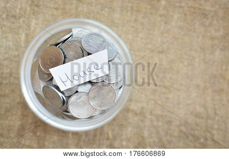 Glass Jar Filled With Coins Labeled With The Words House. View From Above. Background Of Burlap. The