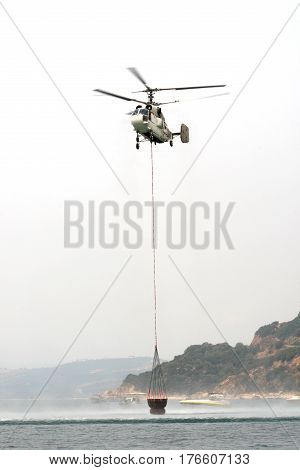 OURANOUPOLI GREECE - AUG 92012: Russian helicopter Kamov ka-32 refills water from sea as it hepls on the massive wildfires near Ouranoupoli and Mt. Athos Peninsula on August 9 2012 in Ouranoupoli Greece
