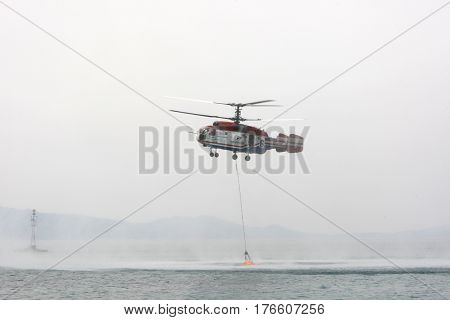 OURANOUPOLI GREECE - AUG 9 2012: Russian helicopter Kamov ka-32 refills water from sea as it hepls on the massive wildfires near Ouranoupoli and Mt. Athos Peninsula on August 9 2012 in Ouranoupoli Greece