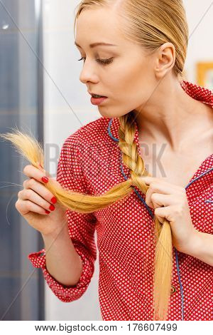 Blonde Woman Looking At Her Hair Ends