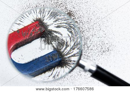 Magnet Attracting Iron Power With Magnetic Force Through Magnifying Glass. Scientific Experiment In