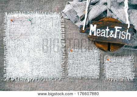 Rectangle pieces of white burlap pinned as frames on gray burlap background. Wood signboard with text 'Meat and fish' on draped canvas in the corner. Rustic style eco-friendly universal template