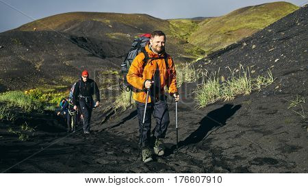man hiker on the trail in the Islandic mountains. Trek in National Park Landmannalaugar, Iceland. valley is covered with volcano asher.