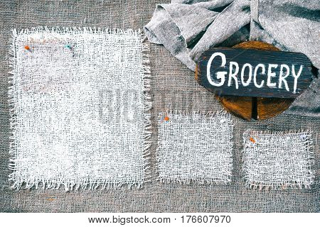 Rectangle pieces of white burlap pinned as various frames on gray burlap background. Wood signboard with text 'Grocery' on draped canvas in the corner. Rustic style eco-friendly template