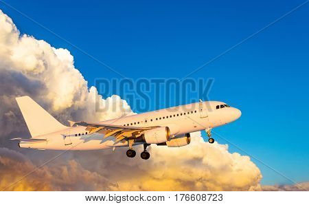 Airplane at fly on the sky with clouds sunset.