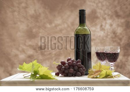 Background image of a red wine bottle with two glasses, red grapes and vine leaves