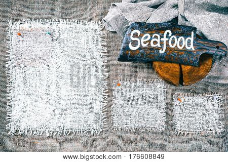 Rectangle pieces of white burlap pinned as various frames on gray burlap background. Wood signboard with text 'Seafood' on draped canvas in the corner. Rustic style eco-friendly template
