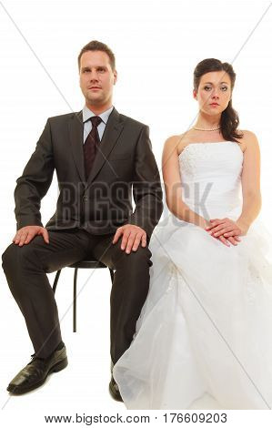 Unwanted marriage bad life decisions concept. Serious groom in suit and bride wearing white dress sitting together and waiting for wedding isolated.