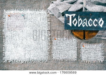 Rectangle pieces of white burlap pinned as various frames on gray burlap background. Wood signboard with text 'Tobacco' on draped canvas in the corner. Rustic style eco-friendly template