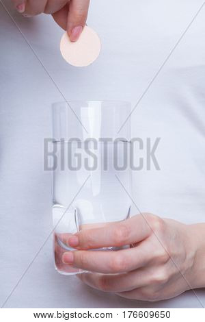 Vitamins health medicines. Person throwing vitamin mineral supplement effervescent tablet into glass of water. Studio shot on white background