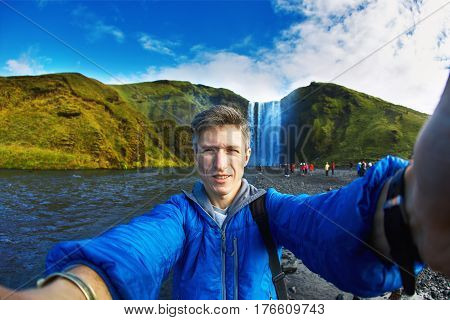 man hiker photographer taking selfie on the mountains background in Iceland