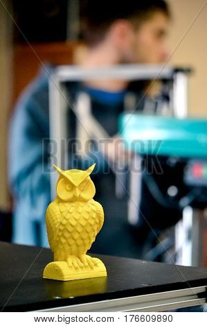 Object printed on a 3d printer close-up in the workshop. Automatic three dimensional 3d printer performs plastic yellow colors modeling in laboratory. Progressive modern additive technology