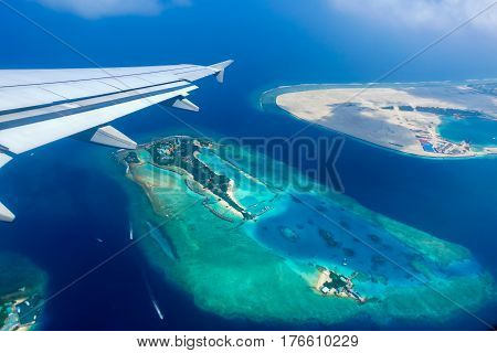 Aerial view of tropical islands and atolls in the Maldives from a plane window