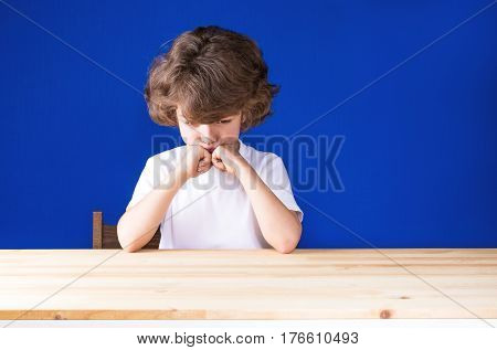 Curly cute young boy resting his head on her hands looking sad on a wooden table. Close-up. Blue background.