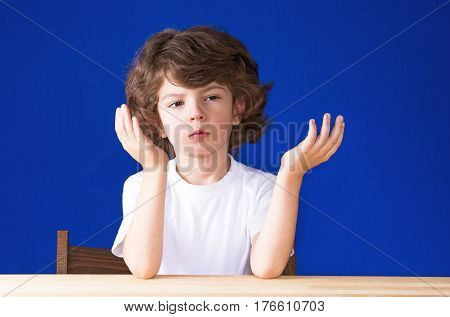 Curly cute boy raised his hands palms up intently looking into the camera. Blue background.