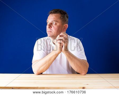 Angry man sitting behind a wooden desk and looking away. Blue background.