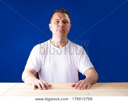 A man sitting at a wooden table and looking at the camera. Blue background.