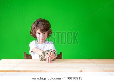 Curly cute boy sitting at a table with his hands bound by a chain and sadly looks at the camera. Close-up. Green background.