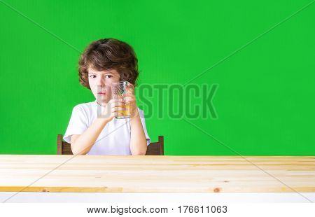 The curly-haired pretty boy holding a glass of juice stares into the camera. Close-up. Green background.