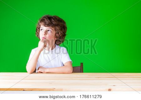 The curly-haired pretty boy stares right up sitting at a table. Close-up. Green background.