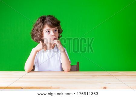 The curly-haired pretty boy looks up in surprise sitting at the table. Close-up. Green background.