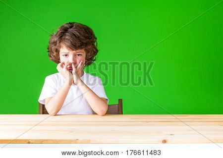 Curly resentful boy touching face with her hands sad looking at the camera. Close-up. Green background.