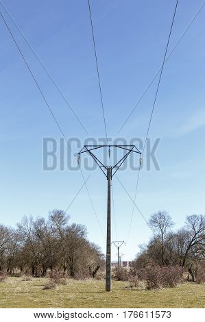 Turret with high voltage electricity cables on a fountain of blue sky