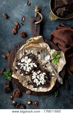 Chocolate brownie cake dessert with nuts on dark background directly above flat lay