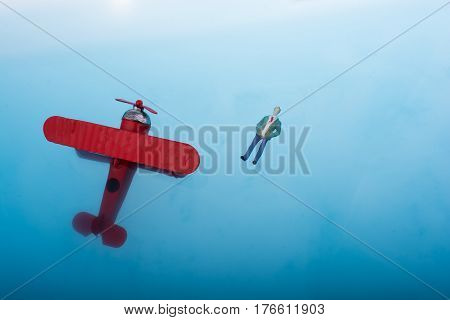 Hand holding a model airplane and a man figurine in blue water