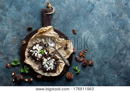 Chocolate brownie cake dessert with nuts on dark background directly above copy space flat lay